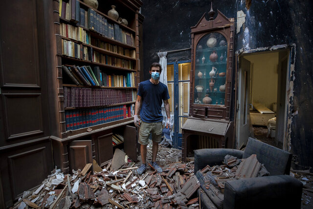 Said Al Assaad, 24, poses for a photograph inside his grandfather's destroyed villa after Tuesday's explosion in the seaport of Beirut, Lebanon, Thursday, Aug. 6, 2020. The gigantic explosion in Beirut on Tuesday tore through homes, blowing off doors and windows, toppling cupboards, and sent flying books, shelves, lamps and everything else. Within a few tragic seconds, more than a quarter of a million people of the Lebanese capital's residents were left with homes unfit to live in. Around 6,200 buildings are estimated to be damaged. (AP Photo/Hassan Ammar)