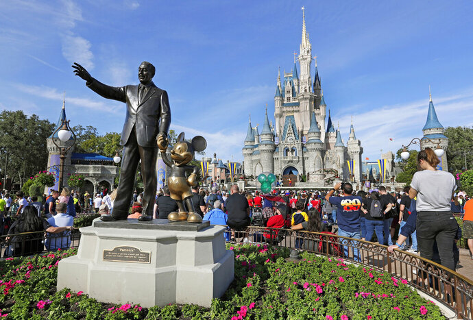 FILE - In this Jan. 9, 2019 photo, guests watch a show near a statue of Walt Disney and Micky Mouse in front of the Cinderella Castle at the Magic Kingdom at Walt Disney World in Lake Buena Vista, part of the Orlando area in Fla.  SeaWorld and Universal Orlando reopened earlier June 2020,  while Disney plans to reopen in phases starting July 11, 2020.(AP Photo/John Raoux, File)