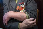 In this photo taken on Monday, Jan. 20, 2020, Yevgeny Kovalyov, 92, one of the Auschwitz concentration camp's survivors, shows the camp's identification number tattooed on his arm during an interview with the Associated Press at his flat in Moscow, Russia. Kovalyov was sent to Auschwitz in 1943. (AP Photo/Alexander Zemlianichenko)