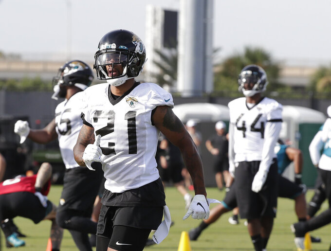 Jacksonville Jaguars cornerback A.J. Bouye (21) warms up with teammates during an NFL football practice at the teams training facility, Friday, July 26, 2019, in Jacksonville, Fla. (AP Photo/John Raoux)