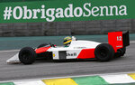Driver Bruno Senna steers the McLaren used by the Brazilian F1 driver Ayrton Senna in 1988, at the Interlagos racetrack in Sao Paulo, Brazil, Thursday, Nov. 14, 2019. (AP Photo/Nelson Antoine)