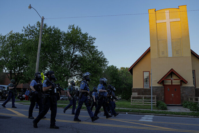 FILE - St. Paul Police officers move in on a crowd past a church, Thursday, May 28, 2020, in St. Paul, Minn.  The Rev. Charles Graham and other Twin Cities faith leaders who minister to communities historically ravaged by racial injustice know their neighborhoods are also the most vulnerable to poverty and crime. Most of the worst looting and vandalism this week struck long-established Native and African American areas that more recently became home to large groups of Hmong, Somali and Latino migrants.(AP Photo/Julio Cortez)