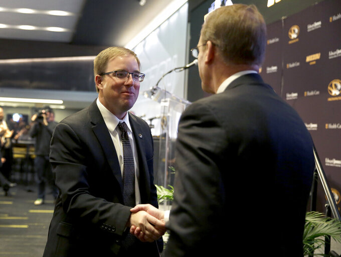 Eliah Drinkwitz, left, stops to shake hands with Mizzou Director of Athletics Jim Sterk as Drinkwitz heads to the stage to be introduced as the new NCAA college football head coach at the University of Missouri, Tuesday, Dec. 10, 2019, in Columbia, Mo. Drinkwitz becomes the 33rd head football coach at Missouri after coaching the 2019 season at Appalachian State. (AP Photo/Jeff Roberson)