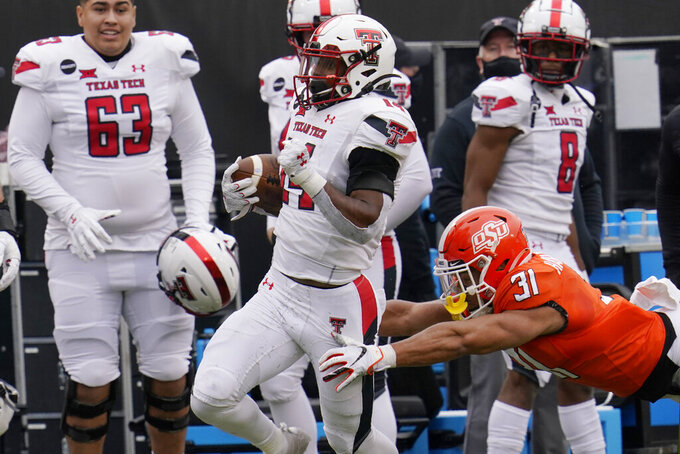 Oklahoma State safety Kolby Harvell-Peel (31) makes a diving attempt at a tackle as Texas Tech running back Xavier White (14) carries for a 70-yard touchdown in the second half an NCAA college football game in Stillwater, Okla., Saturday, Nov. 28, 2020. (AP Photo/Sue Ogrocki)