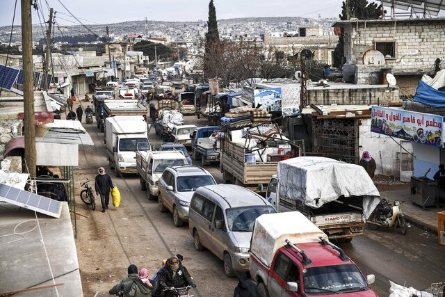 FILE - In this Feb. 15, 2020, file photo, civilians flee from Idlib toward the north to find safety inside Syria near the border with Turkey. An international human rights group said Thursday, Oct. 15, 2020 that a yearlong military campaign by Syrian and Russian forces that repeatedly attacked civilian targets in the last rebel stronghold in northwestern Syria constituted apparent war crimes and may amount to crimes against humanity. (AP Photo/File)