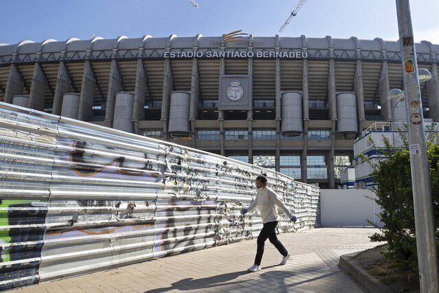 A woman wearing a protective mask walks past Real Madrid's Santiago Bernabeu stadium in Madrid, Spain, Friday, March 13, 2020. Real Madrid have said its players were being placed in isolation after one of the club's basketball players, who share facilities with Madrid's soccer players, tested positive for the COVID-19 coronavirus. That led to the instant decision by the Spanish league to bring matches to a halt for the next two rounds. For most people, the new coronavirus causes only mild or moderate symptoms. For some it can cause more severe illness, especially in older adults and people with existing health problems. (AP Photo/Paul White)