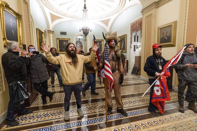 FILE - In this Wednesday, Jan. 6, 2021 file photo, supporters of President Donald Trump are confronted by U.S. Capitol Police officers outside the Senate Chamber inside the Capitol in Washington. On Friday, Jan. 8, 2021, The Associated Press reported on stories circulating online incorrectly asserting that Capitol rioters were antifa activists. At center is Jake Angeli, wearing fur hat with horns, a regular at pro-Trump events and a known follower of QAnon. (AP Photo/Manuel Balce Ceneta)