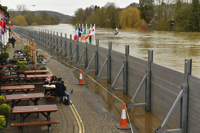 People eating at a pub in front of temporary flood defences set up in the aftermath of Storm Dennis, in Bewdley, England, Wednesday Feb. 19, 2020. Flood-hit communities are braced for further heavy rain as river levels continue to threaten to breach barriers. (Jacob King/PA via AP)