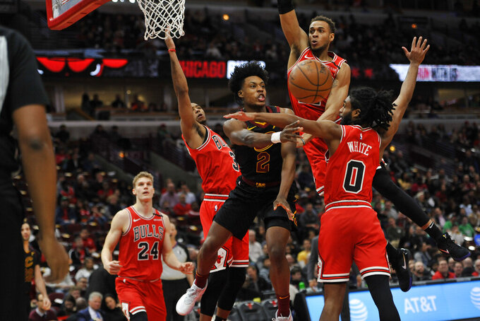 File-This March 10, 2020, file photo shows Cleveland Cavaliers' Collin Sexton (2) passing the ball as Chicago Bulls' Coby White (0), Daniel Gafford (12), Shaquille Harrison (3) and Lauri Markkanen (24) defend during the first half of an NBA basketball game in Chicago. The NBA's interrupted season and invitation-only gathering in Florida to finish it due to the pandemic hurt every team to varying degrees. It devastated the Cleveland Cavaliers. (AP Photo/Paul Beaty, File)