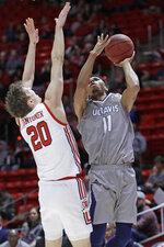 UC Davis guard Caleb Fuller (11) shoots as Utah forward Mikael Jantunen (20) defends during the first half of an NCAA college basketball game Friday, Nov. 29, 2019, in Salt Lake City. (AP Photo/Rick Bowmer)