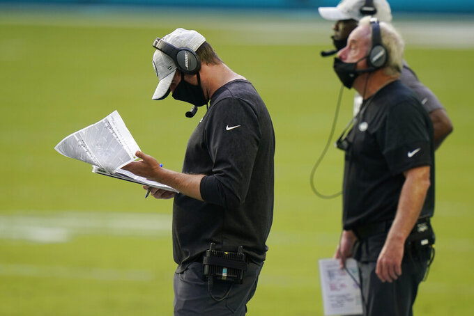 New York Jets head coach Adam Gase looks at copies of plays during the first half of an NFL football game against the Miami Dolphins, Sunday, Oct. 18, 2020, in Miami Gardens, Fla. (AP Photo/Lynne Sladky)