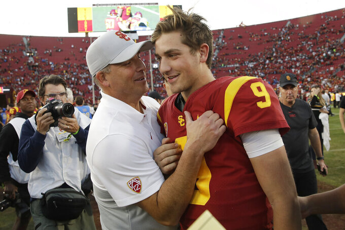 Southern California head coach Clay Helton, left, smiles at quarterback Kedon Slovis (9) after a 52-35 win over UCLA in an NCAA college football game, Saturday, Nov. 23, 2019, in Los Angeles. (AP Photo/Marcio Jose Sanchez)