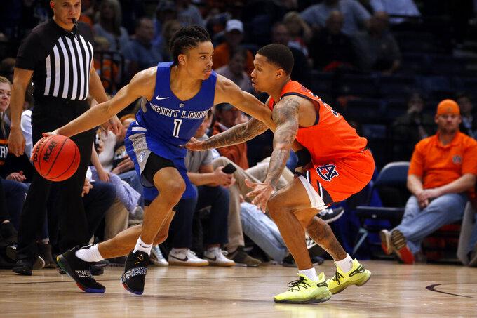 Saint Louis guard Yuri Collins (1) dribbles around Auburn guard J'Von McCormick (5) during the second half of an NCAA college basketball game Saturday, Dec. 14, 2019, in Birmingham, Ala. (AP Photo/Butch Dill)