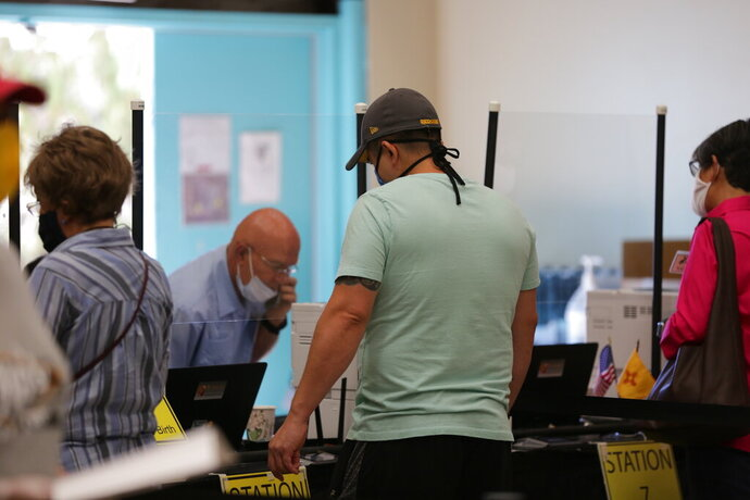 Democratic primary voter Sergio Marquez, 34, waits for poll workers to sort out his ballot during primary voting on Tuesday, June 2, 2020, in Santa Fe, New Mexico. Marquez said an absentee ballot he requested never came and that a server issue at the polling place delayed him from voting in person. He The problem was resolved within an hour and he was able to vote. (AP Photo/Cedar Attanasio)