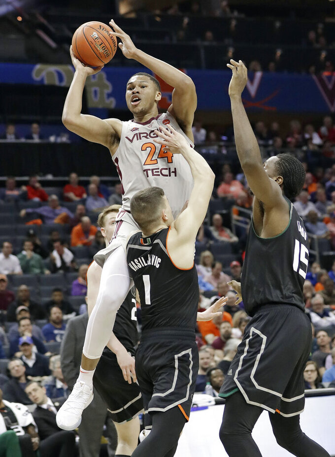 Virginia Tech's Kerry Blackshear Jr. (24) shoots against Miami's Dejan Vasiljevic (1) and Ebuka Izundu (15) during the first half of an NCAA college basketball game in the Atlantic Coast Conference tournament in Charlotte, N.C., Wednesday, March 13, 2019. (AP Photo/Chuck Burton)