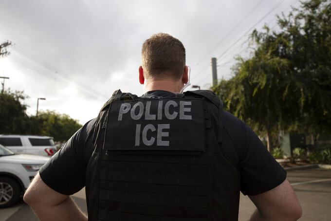 FILE - In this July 8, 2019, file photo, a U.S. Immigration and Customs Enforcement (ICE) officer watches during an operation in Escondido, Calif. A Chinese pro-democracy activist is being detained by the Biden administration under what his advocates allege are charges falsified by Beijing so he can be deported and punished for his advocacy. The man's attorneys have asked U.S. Immigration and Customs Enforcement to release him from custody while his asylum application is reviewed. (AP Photo/Gregory Bull, File)