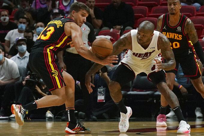 Miami Heat forward P.J. Tucker (17) and Atlanta Hawks guard Bogdan Bogdanovic (13) go after the ball during the first half of a preseason NBA basketball game, Monday, Oct. 4, 2021, in Miami. (AP Photo/Marta Lavandier)