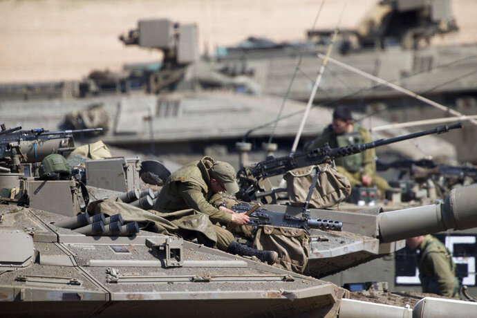 Israeli soldiers work on their tanks at a gathering area near the Israel-Gaza border, Israel, Tuesday, March 26, 2019. Israeli Prime Minister Benjamin Netanyahu returned home from Washington on Tuesday, heading straight into military consultations after a night of heavy fire as Israeli aircraft bombed Gaza targets and the strip's militants fired rockets into Israel. (AP Photo/Ariel Schalit)