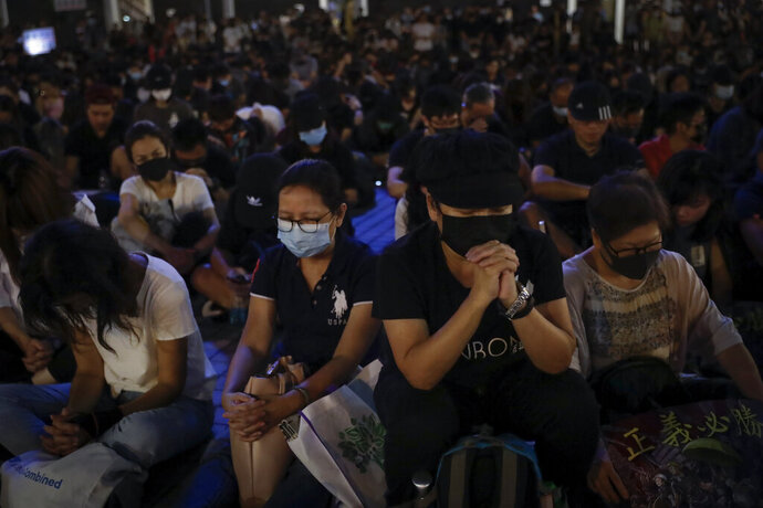 Protesters attend a prayer rally at Edinburgh Place in Hong Kong, Saturday, Oct. 19, 2019. Hong Kong pro-democracy protesters are set for another weekend of civil disobedience as they prepare to hold an unauthorized protest march to press their demands. (AP Photo/Mark Schiefelbein)