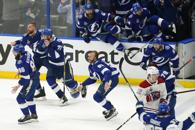 Members of the Tampa Bay Lightning rush the ice after the team defeated the Montreal Canadiens in Game 5 of the NHL hockey Stanley Cup finals, Wednesday, July 7, 2021, in Tampa, Fla. (AP Photo/Gerry Broome)