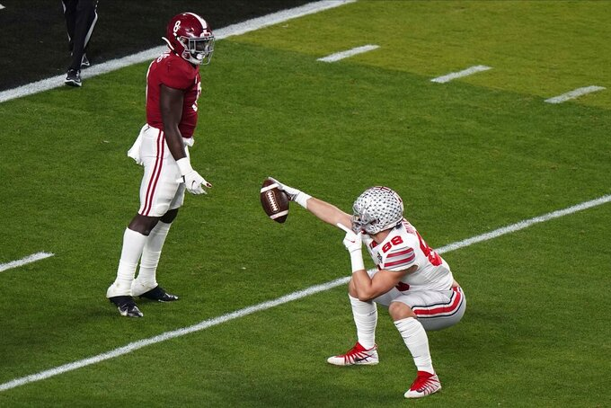 Ohio State tight end Jeremy Ruckert celebrates after a catch as Alabama linebacker Christian Harris looks on during the first half of an NCAA College Football Playoff national championship game, Monday, Jan. 11, 2021, in Miami Gardens, Fla. (AP Photo/Wilfredo Lee)