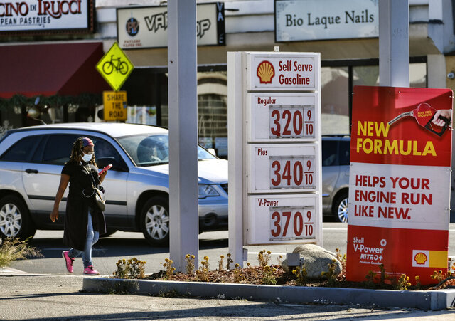 A masked pedestrian walks past a self-service gas station in the Sherman Oaks section of Los Angeles, Sunday, Dec. 6, 2020. The average U.S. price of regular-grade gasoline rose 4 cents a gallon over the past two weeks to $2.22. Industry analyst Trilby Lundberg of the Lundberg Survey said that a rise in crude oil prices spurred the increase. She says demand for gasoline remains low in the United States due to the coronavirus pandemic. (AP Photo/Richard Vogel)