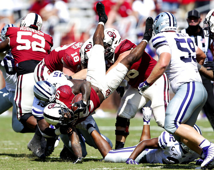 Kansas State defensive tackle Robert Hentz II (15) tackles Oklahoma running back T.J. Pledger (5) during an NCAA college football game in Norman, Okla., Saturday, Sept. 26, 2020. (Ian Maule/Tulsa World via AP)