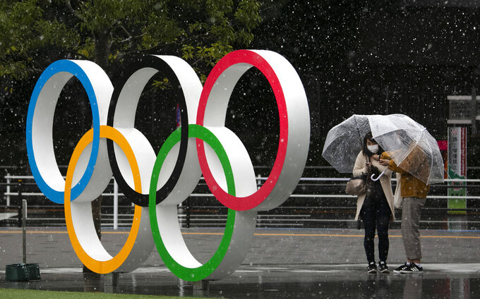 FILE - In this March 14, 2020, file photo, snow falls on the Olympic Rings near the New National Stadium in Tokyo. Day 11 of the postponed Tokyo Olympics finally brought what was feared the most before the pandemic postponed the games for a year: A hot and humid Tokyo summer day. (AP Photo/Jae C. Hong, File)