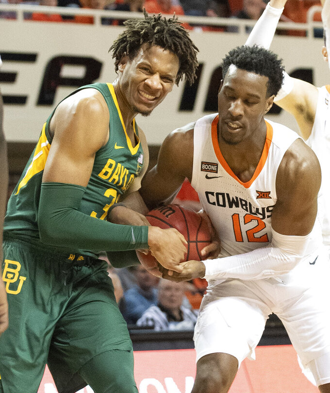 Baylor forward Freddie Gillespie (33) ties up the ball with Oklahoma State forward Cameron McGriff (12) during the second half of an NCAA college basketball game in Stillwater, Okla., Saturday, Jan. 18, 2020. Baylor defeated Oklahoma State 75-68. (AP Photo/Brody Schmidt)