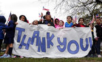Students from Salyer Elementary School wave flags and signs as the train carrying the body of former president George H.W. Bush travels past their school on the way to Bush's final internment Thursday, Dec. 6, 2018, in Spring, Texas. (AP Photo/Michael Wyke)