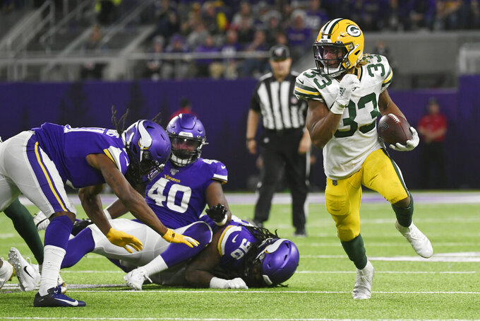 Green Bay Packers running back Aaron Jones (33) carries on a 56-yard touchdown run during the second half of the team's NFL football game against the Minnesota Vikings, Monday, Dec. 23, 2019, in Minneapolis. (AP Photo/Craig Lassig)