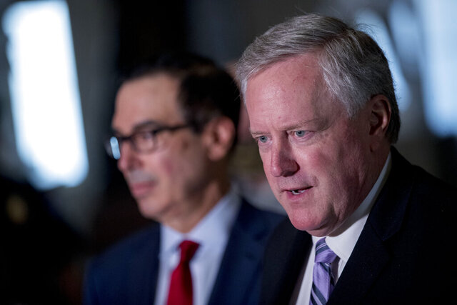 White House Chief of Staff Mark Meadows, right, accompanied by Treasury Secretary Steven Mnuchin, left, speaks to reporters following a meeting with House Speaker Nancy Pelosi of Calif. and Senate Minority Leader Sen. Chuck Schumer of N.Y. as they continue to negotiate a coronavirus relief package on Capitol Hill in Washington, Friday, Aug. 7, 2020. (AP Photo/Andrew Harnik)