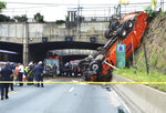 First responders work the scene of a truck accident in Union, City, N.J., not far from the Lincoln Tunnel, Wednesday, July 3, 2019. The overturned garbage truck blocked a major route out of New York City during the evening commute before the Fourth of July weekend. (Michaelangelo Conte/The Jersey Journal via AP)
