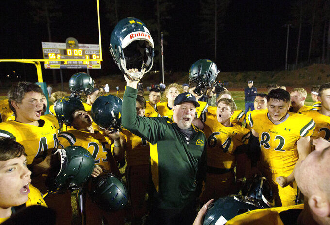 FILE - In this Nov. 15, 2019 file photo, Paradise High School head football coach Rick Prinz, center, celebrates with his team after defeating Live Oak High School  in their Northern California Division III playoff game in Paradise, Calif.  Paradise, the  Northern California high school football team is preparing to play for a championship one year after most of the players and coaches lost their homes to a wildfire that nearly destroyed their town. Paradise High School will face Sutter Union High School on Saturday, Nov. 30  for the Northern Section Division III championship.(AP Photo/Rich Pedroncelli, File)