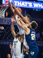 Wake Forest guard Ian DuBose (11) and forward Ody Oguama (33) and Georgia Tech forward Rodney Howard (24) reach for a rebound during an NCAA college basketball game Friday, March 5, 2021, in Winston-Salem, N.C. (Andrew Dye/The Winston-Salem Journal via AP)