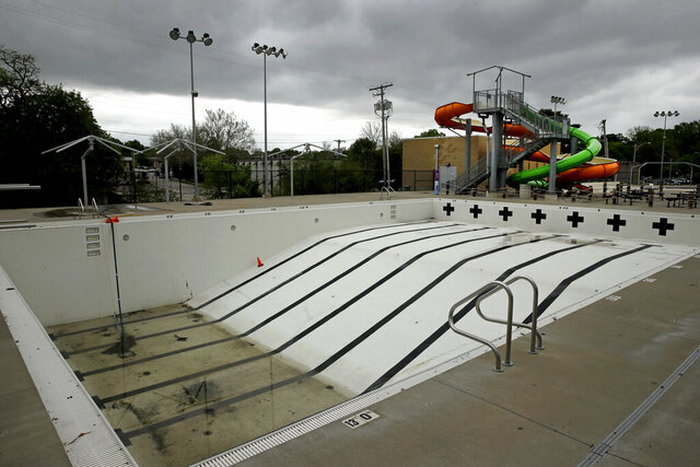 In this photo taken Friday, May 15, 2020, the public pool in Mission, Kan. is lifeless as plans remain in place to keep the pool closed for the summer to help prevent the spread of COVID-19. As warm weather approaches and many public pools remain closed there has been a surge of people using backyard pools as well at taking to water activities on lakes and rivers to get out and cool off. (AP Photo/Charlie Riedel)