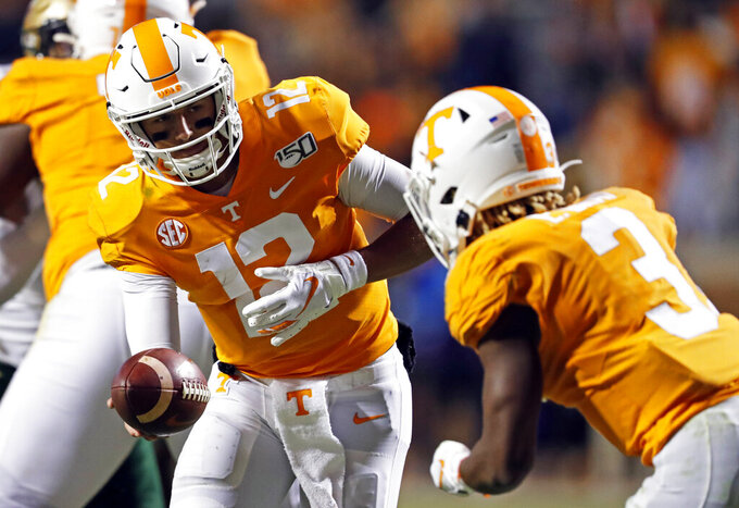 Tennessee quarterback J.T. Shrout (12) hands the ball off to running back Eric Gray (3) in the second half of an NCAA college football game against UAB, Saturday, Nov. 2, 2019, in Knoxville, Tenn. (AP Photo/Wade Payne)