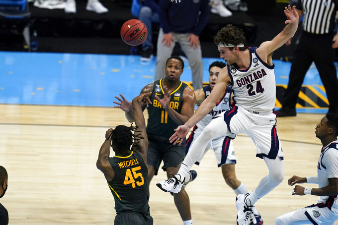 Baylor guard Davion Mitchell (45) passes around Gonzaga forward Corey Kispert (24) during the first half of the championship game in the men's Final Four NCAA college basketball tournament, Monday, April 5, 2021, at Lucas Oil Stadium in Indianapolis. (AP Photo/Michael Conroy)