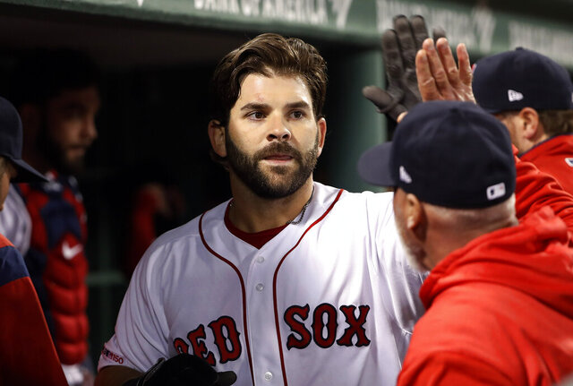 FILE - In this Thursday, April 11, 2019 file photo, Boston Red Sox's Mitch Moreland is greeted in the dugout after his home run against the Toronto Blue Jays during the seventh inning of a baseball game at Fenway Park in Boston. First baseman Mitch Moreland is staying with the Boston Red Sox, agreeing Tuesday, Jan. 28, 2020 to a one-year contract that guarantees $3 million. Moreland gets a $2.5 million salary this year, and Boston has a $3 million team option for 2021 with a $500,000 buyout.(AP Photo/Winslow Townson, File)