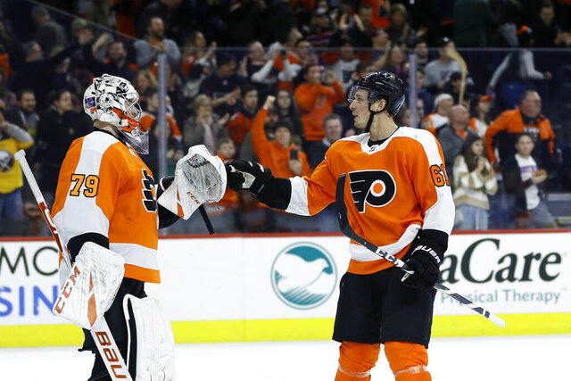 Philadelphia Flyers' Carter Hart (79) and Justin Braun (61) celebrate after an NHL hockey game against the Buffalo Sabres, Saturday, March 7, 2020, in Philadelphia. Philadelphia won 3-1. (AP Photo/Matt Slocum)