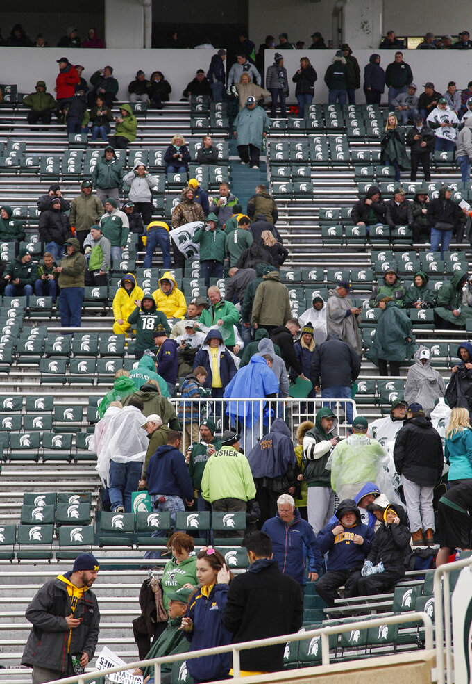 Fans begin to return to their seats in Spartan Stadium following a weather delay in the Michigan-Michigan State NCAA college football game, Saturday, Oct. 20, 2018, in East Lansing, Mich. (AP Photo/Al Goldis)
