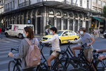 Tourists wearing face masks to prevent the spread of COVID-19 ride bicycles in central Athens, Saturday, Oct. 31, 2020. Greece saw a jump in the number of confirmed coronavirus cases during last week, and Prime Minister Kyriakos Mitsotakis is widely expected to announce new social restrictions. (AP Photo/Yorgos Karahalis)