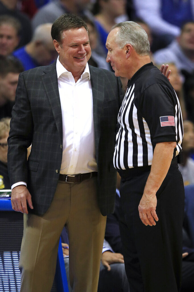 Kansas coach Bill Self, left, talks with referee Joe DeRosa, right, during the first half of the team's exhibition NCAA college basketball game against Pittsburg State in Lawrence, Kan., Thursday, Oct. 31, 2019. (AP Photo/Orlin Wagner)
