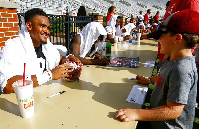 Alabama quarterback Jalen Hurts signs an autograph for Brody Bankston after the NCAA college football team's practice, Saturday, Aug. 4, 2018, in Tuscaloosa, Ala. (AP Photo/Butch Dill)