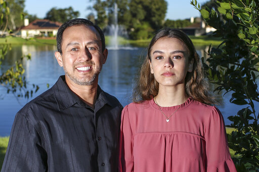 Portrait of Mitch Arbelaez and his daughter Jayden in Jacksonville, Fla., Wednesday, Oct. 13, 2021.  Banned from the Florida hospital room where her mother lay dying of COVID-19, Jayden Arbelaez pitched an idea to construction employees working nearby.  The workers gave the 17-year-old a yellow vest, boots, a helmet and a ladder to climb onto a section of roof so she could look through the window and see her mother, Michelle Arbelaez, alive one last time. (AP Photo/Gary McCullough)