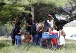 Venezuelan migrants rest under a tree near the International bridge Tienditas, on the outskirts of Cucuta, Colombia, on the border with Venezuela, Tuesday, Feb. 5, 2019. Venezuelan opposition leader Juan Guaido is moving ahead with plans to try to bring in humanitarian aid through the Colombian border city of Cucuta, where the U.S. government will transport and store food and medical supplies destined for Venezuela. (AP Photo/Fernando Vergara)
