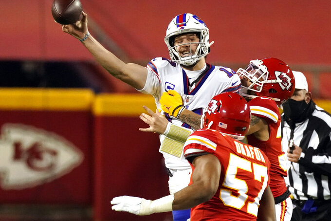 Buffalo Bills quarterback Josh Allen (17) throws a pass as he is pressured by Kansas City Chiefs defenders during the first half of the AFC championship NFL football game, Sunday, Jan. 24, 2021, in Kansas City, Mo. (AP Photo/Charlie Riedel)