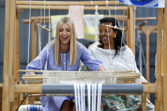 White House senior adviser Ivanka Trump, left, reacts as she tries her hand at a traditional weaving loom at Muya, a manufacturing center of textile and traditional crafts, with Muya founder Sara Abera, Sunday, April 14, 2019, in Addis Ababa, Ethiopia. Trump is visiting Ethiopia and later this week the Ivory Coast to promote a White House global economic program for women. (AP Photo/Jacquelyn Martin)