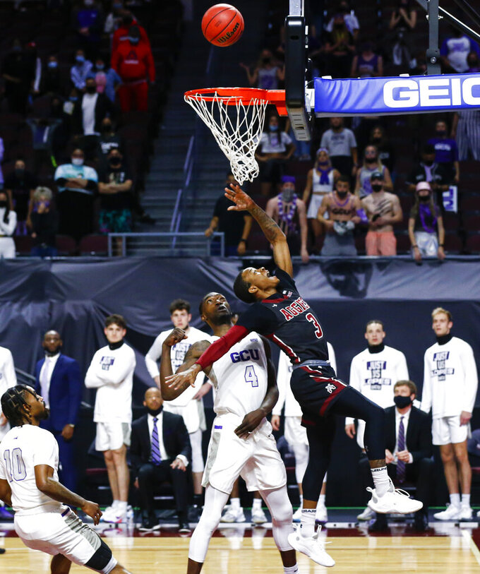 New Mexico State's Evan Gilyard II (3) lays up the ball against Grand Canyon's Oscar Frayer (4) during the first half of an NCAA college basketball game for the championship of the Western Athletic Conference men's tournament Saturday, March 13, 2021, in Las Vegas. (AP Photo/Chase Stevens)