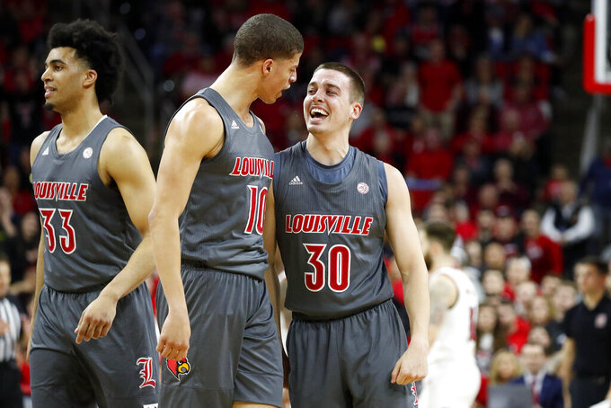 Louisville's Ryan McMahon (30) celebrates one of his 3-point shots with teammate Samuell Williamson (10) during the first half of an NCAA college basketball game against North Carolina State in Raleigh, N.C., Saturday, Feb. 1, 2020. (AP Photo/Karl B DeBlaker)